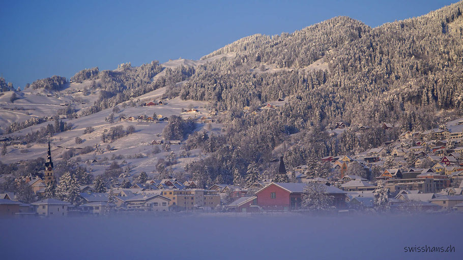 Winterlich verschneiter Hügelzug bei Marbach mit dem Dorf Marbach im Rheintal