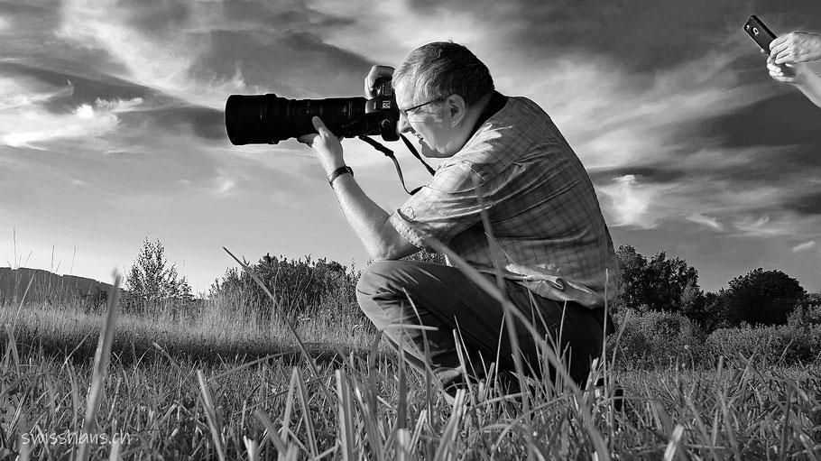 Robert Hangartner kniet in einer Wiese und fotografiert mit dem grossen Teleobjektiv und wird von einem Smartphone fotografiert