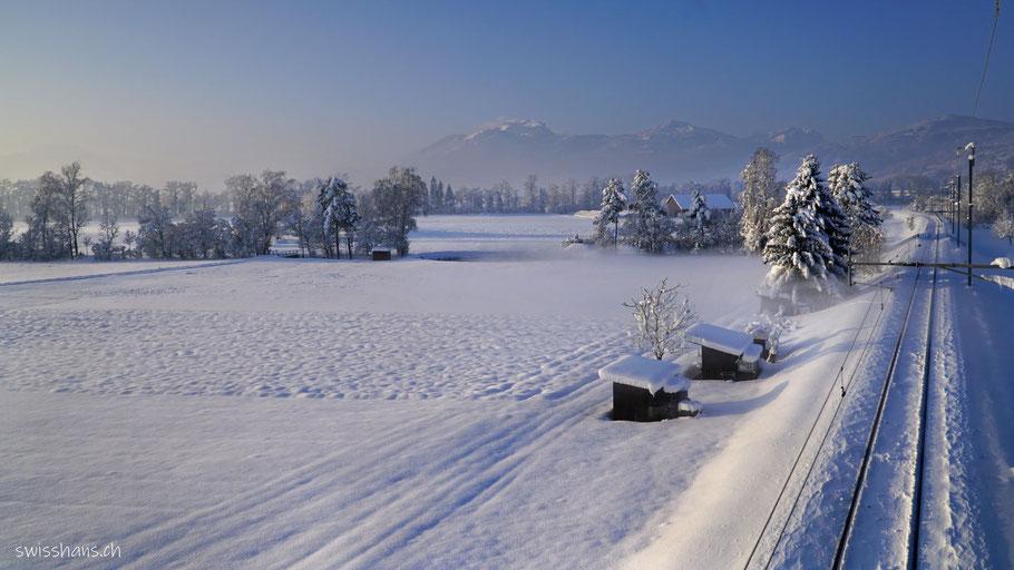 Winterlandschaft  mit Geleisen der Eisenbahn und Schrebergartenhäuschen