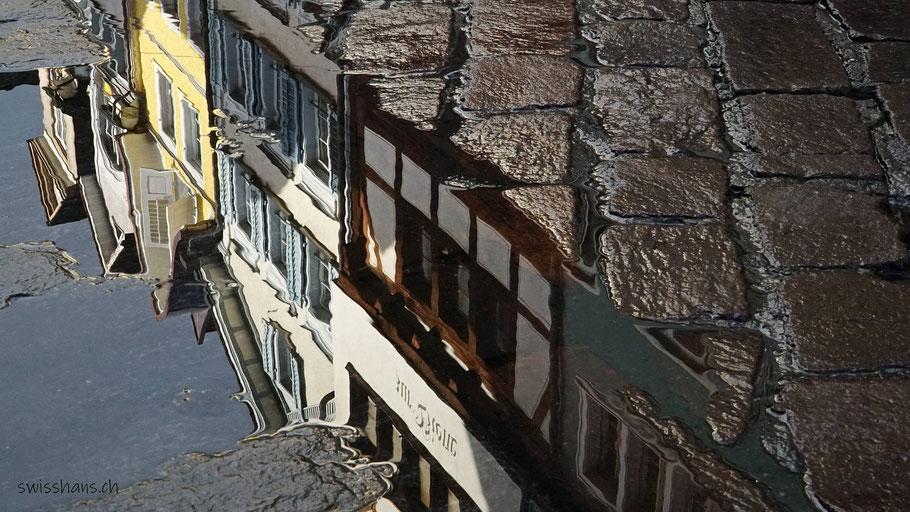 Wasserpfütze auf der Pflästerung der Marktgasse Altstätten mit Spiegelung der antiken Häuser