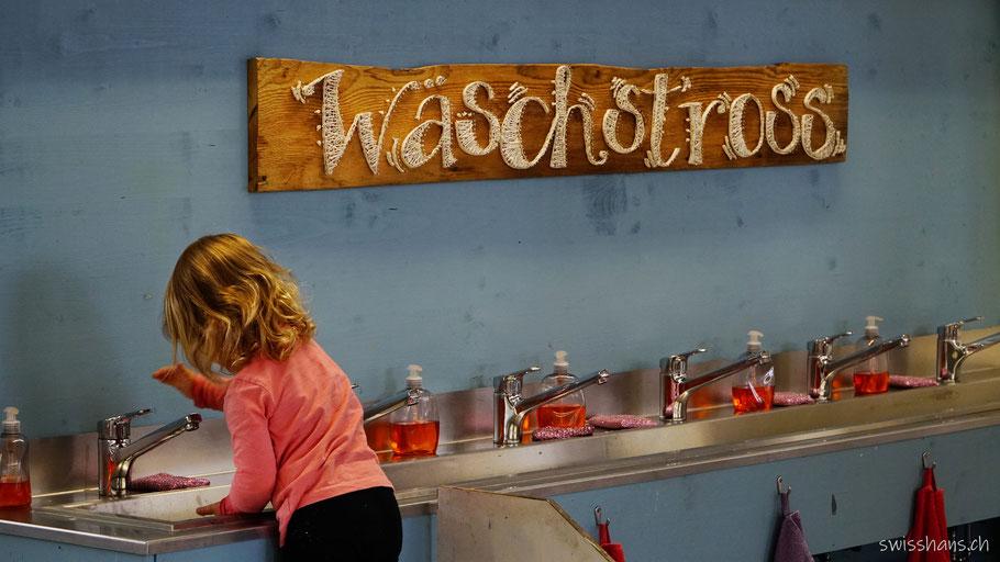 Ein Mädchen reinigt in der Kreativhalle Setzchaschte in Grabs die Hände.