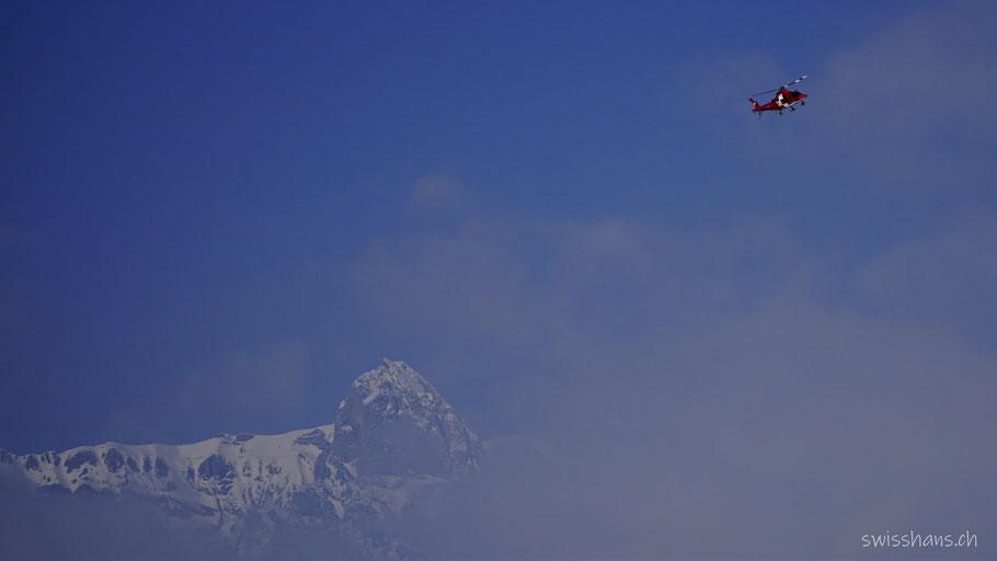 Rettungshelikopter der REGA beim Spital Grabs vor den verschneiten Bergen