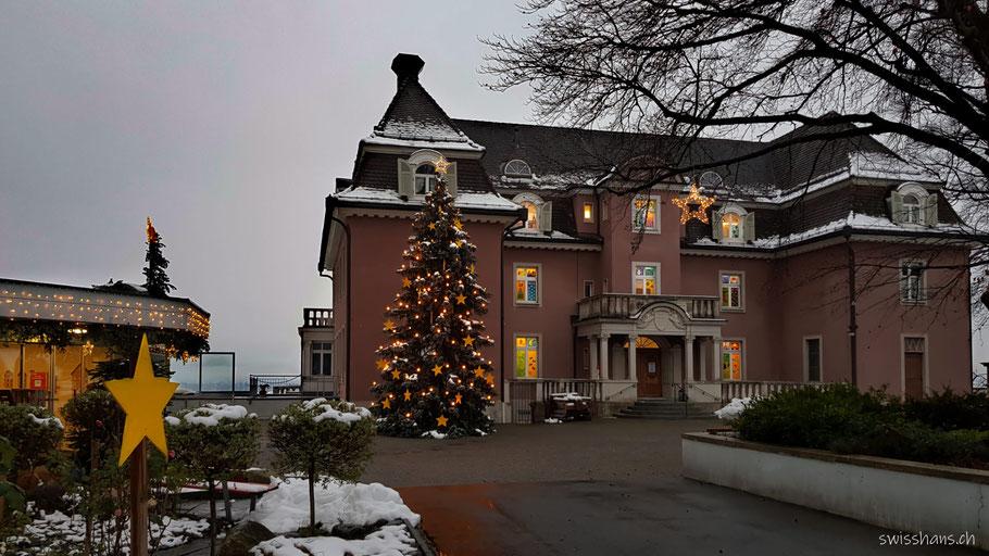 Gebäude mit Christbaum und weihnächtlich geschmückten Fenstern