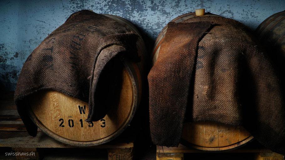 Zwei Whiskyfässer mit braunen Säcken im Keller