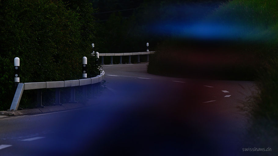 Stossstrasse bei Nacht mit Leitplanke und Strassenpfählen und blauem Licht eines Bikers