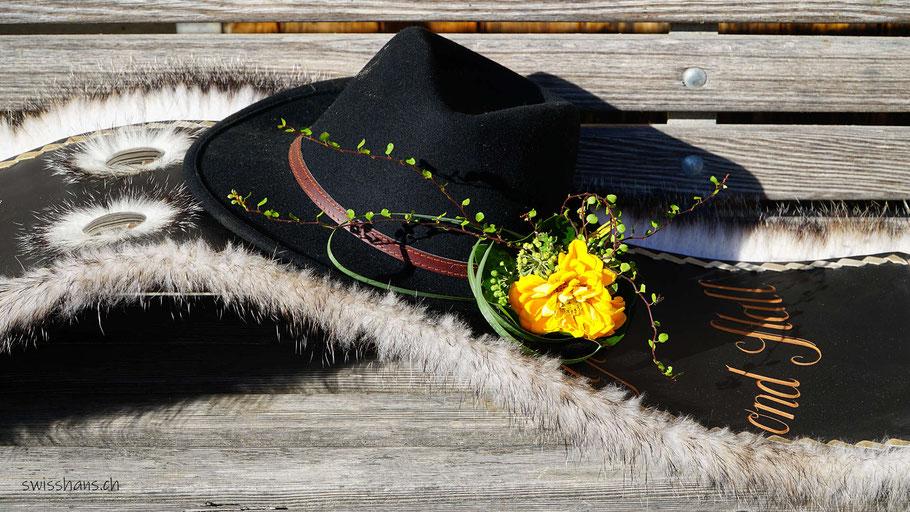 Mit Blume geschmückter Hut auf einem geschmückten Lederriemen für eine Kuh.