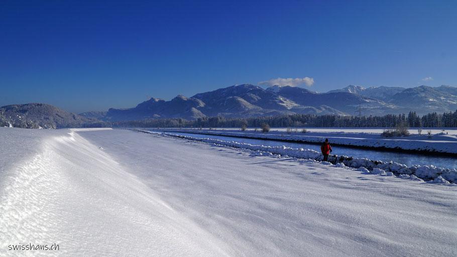 Rhein mit verschneitem Rheinvorland und einem Winterwanderer