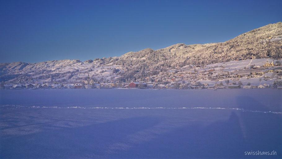 Schneelandschaft bei Marbach im Rheintal. Verschneite Wiese und Hügelzug