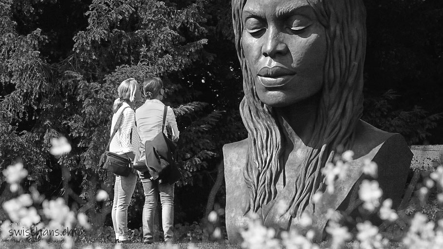 Zwei Frauen stehen vor einer Skulptur einer Frau an der Skulpturenausstellung BadRagartz in Bad Ragaz
