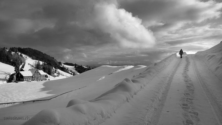 Winterlandschaft mit verschneitem Weg und einer Wanderin bei der Landmark