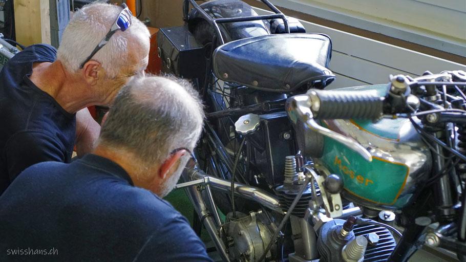 Zwei Besucher des Motorradmuseums Wüst in Oberriet bestaunen ein antikes Motorrad.