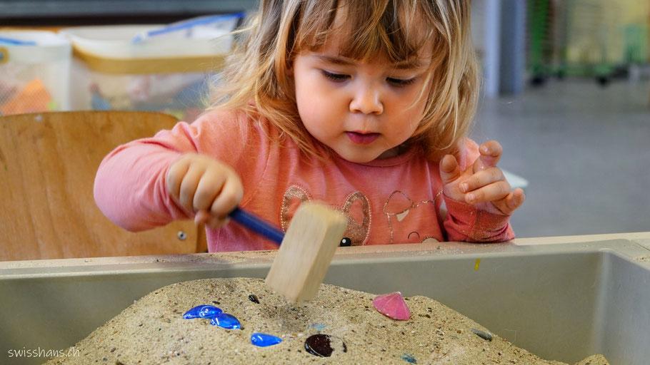 Mädchen schlägt mit einem Holzhammer blaue Perlen in den Zaubersand in der Kreativhalle Setzchaschte in Grabs.