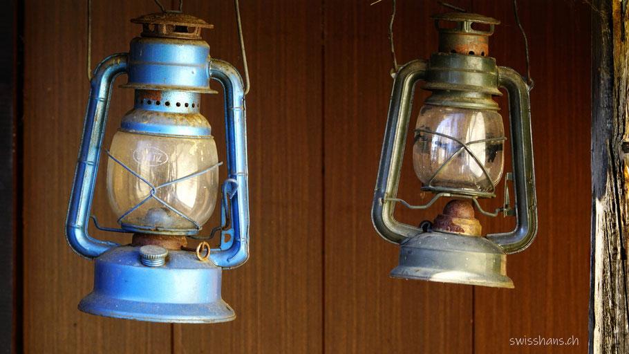 Zwei Petrollampen hängen an der Wand