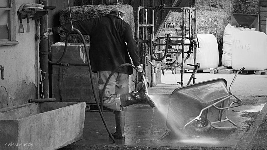 Der Bauer im Werkheim Wyden vom Rhyboot in Balgach spritzt seine Stiefel ab