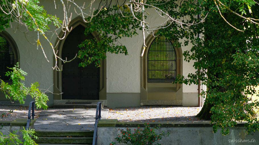 Eingangsbereich der Forstkapelle mit Treppe, Tor und Fenster unter alten Bäumen