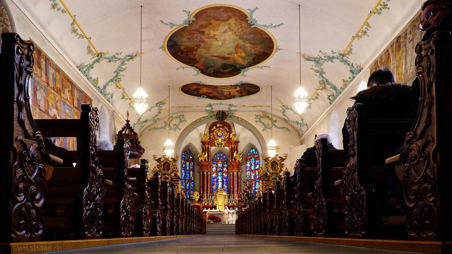 Chorraum der Kirche mit Bankreihen und Blick auf den Altar und die prächtig verzierte Decke.