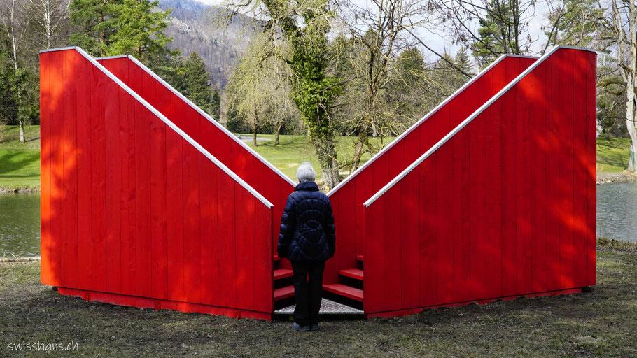 Rote Aussichtsplattform am Giessenparksee im Giessenpark von Bad Ragaz mit Frau.