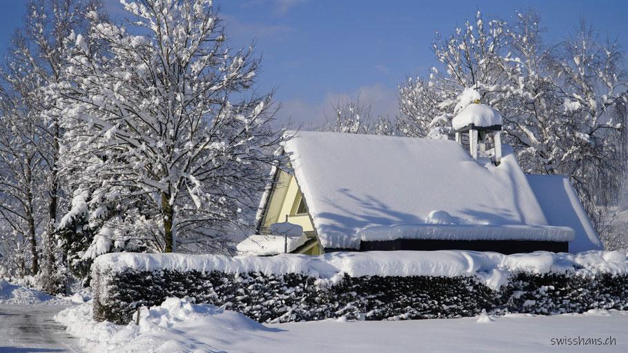 Seitenansicht der Kapelle im Riet bei Oberriet. Geweiht der Maria Knotenlöserin. Schneebedeckte Dächer und Bäume