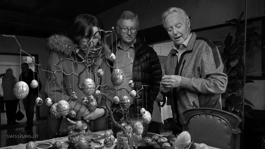 Drei Personen bestaunen geschmückte Ostereier an der Osterausstellung in der Burg Rebstein