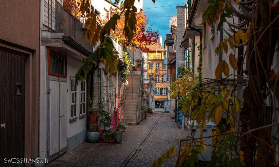 Alte Mauer aus Ziegelsteinen mit offenen Fenstern und blauem Auto davor. Blauer Himmel mit modernem Gebäude
