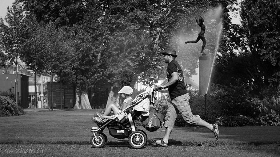 Vater mit Kinderwagen im Park von Rorschach mit Rasensprenger und Statue im Hintergrund