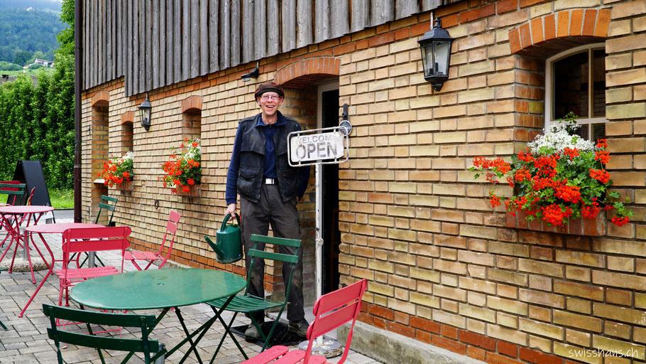 Philipp Mäser vor dem Café Mäser im Feld Marbach mit roten Geranien und Gartentischen