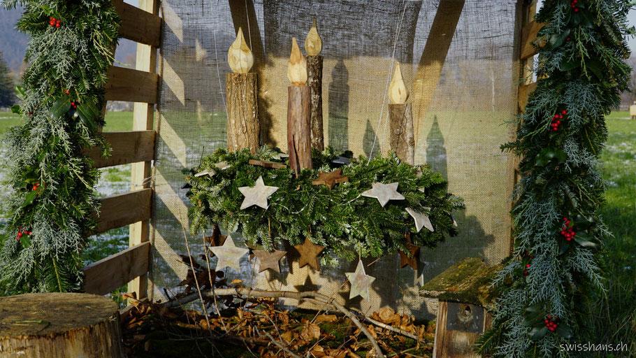 Adventskranz mit Sternen und Kerzen aus Holz in einem Unterstand beim Adventsweg Rebstein -Balgach