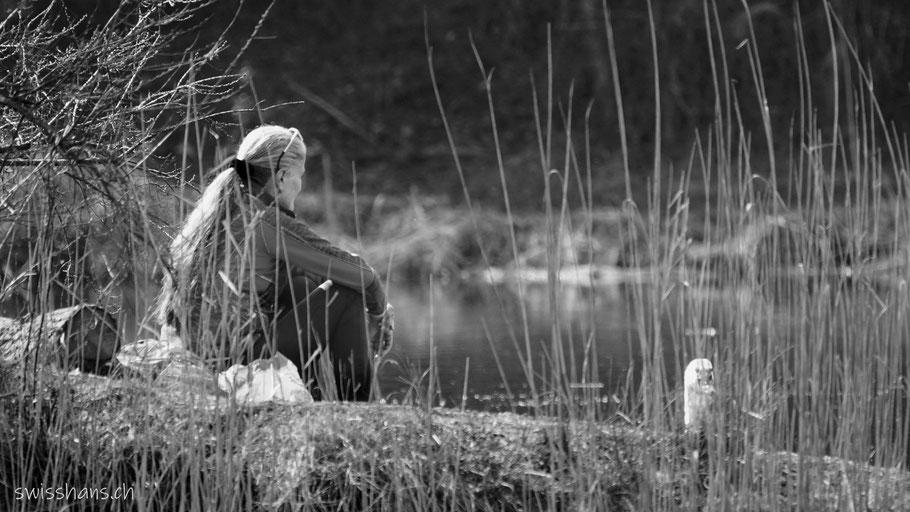 Eine Frau sitzt am Ufer des alten Rheins und betrachtet einen Schwan