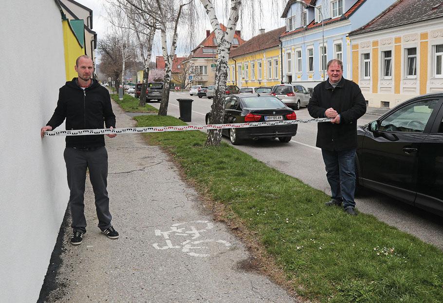 Der kombinierte Geh- und Radweg in der Kurz-Gasse wird drei Meter breit - Sachbearbeiter Mario Don (li.) und Stadtrat Manfred Daniel zeigen die Verbreiterung mit der Messlatte.