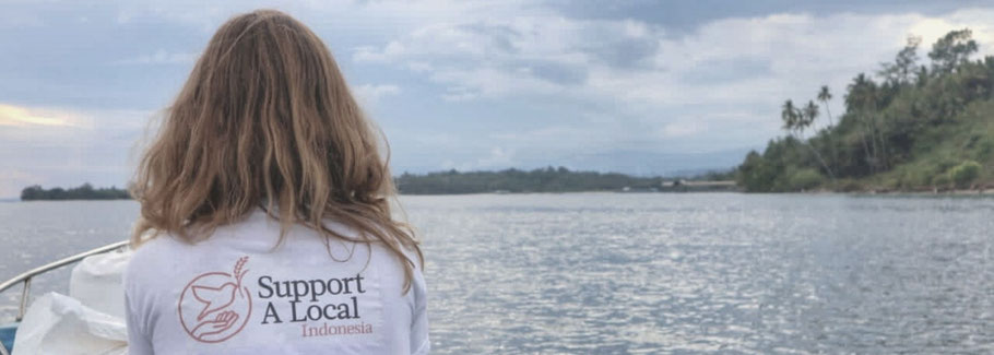 """Corinna on a delivery to a fisher village wearing the t-shirt """"Support a Local"""""""