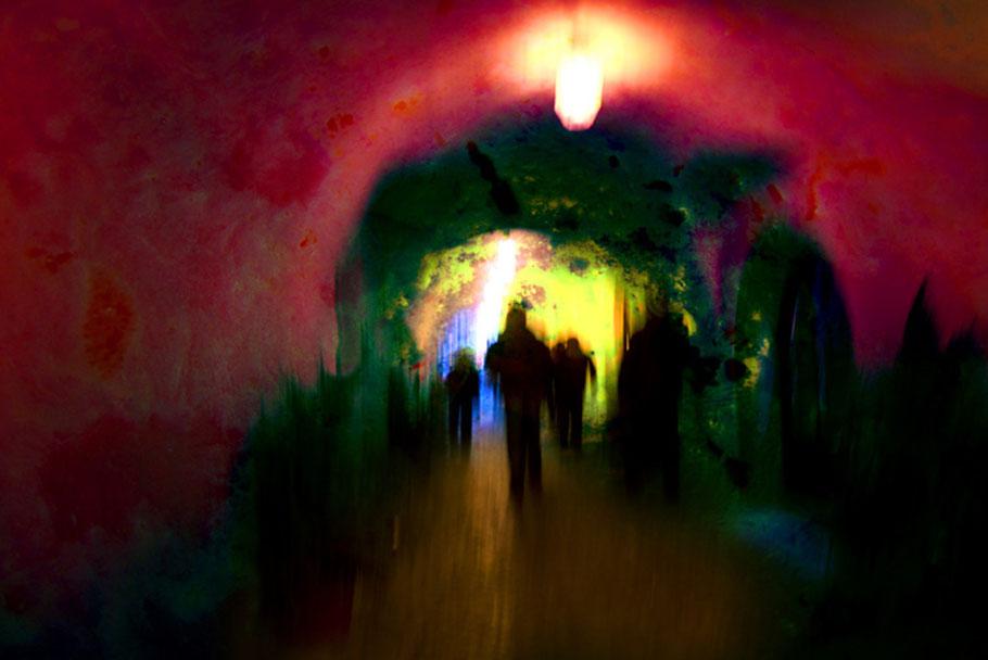 Schemenhafte Gestalten in einen roten Tunnel. Am Ende des Tunnels, blau-gelb-grünes Licht.