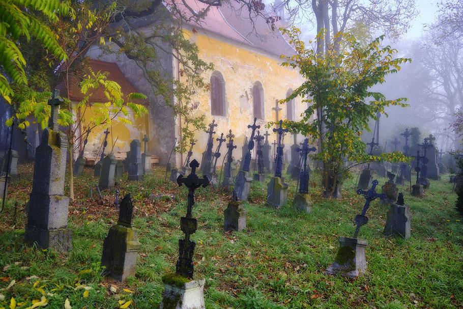 Ahnenforschung. Tschechien, alter deutscher Friedhof mit eisernen Grabkreuzen und Kirche im Morgennebel.