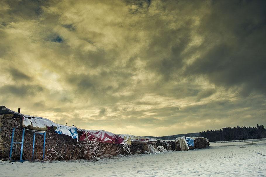 Aufgeschichtetes Brennholz mit farbigen Planen abgedeckt. Verschneite Landschaft. Dramatische Wolken. Sehr schönes Licht.