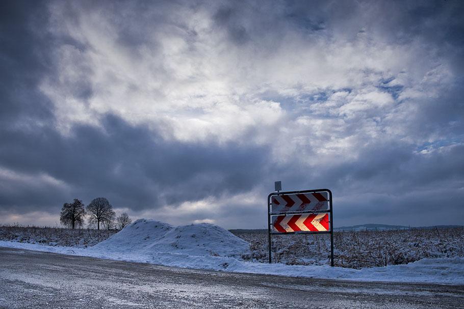 Richtungstafeln, (Verkehrszeichen) in Winterlandschaft. Angestrahlt mit Autoscheinwerfer. Dramatische Wolken.