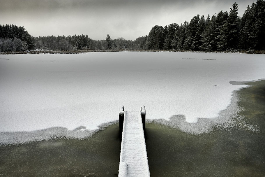 Vordergrung. Schneebedeckter Steg. Grünlich schimmerndes angetautes Eis. Hintergrund. Waldrand, starke Bewölkung.