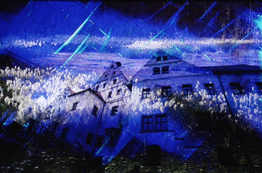 Analoge Ebenentechnik. Häusergiebel in Wolken gehüllt. Die Wolken sind in Wirklichkeit Wollgras. Vorherrschende Farbe Blau.