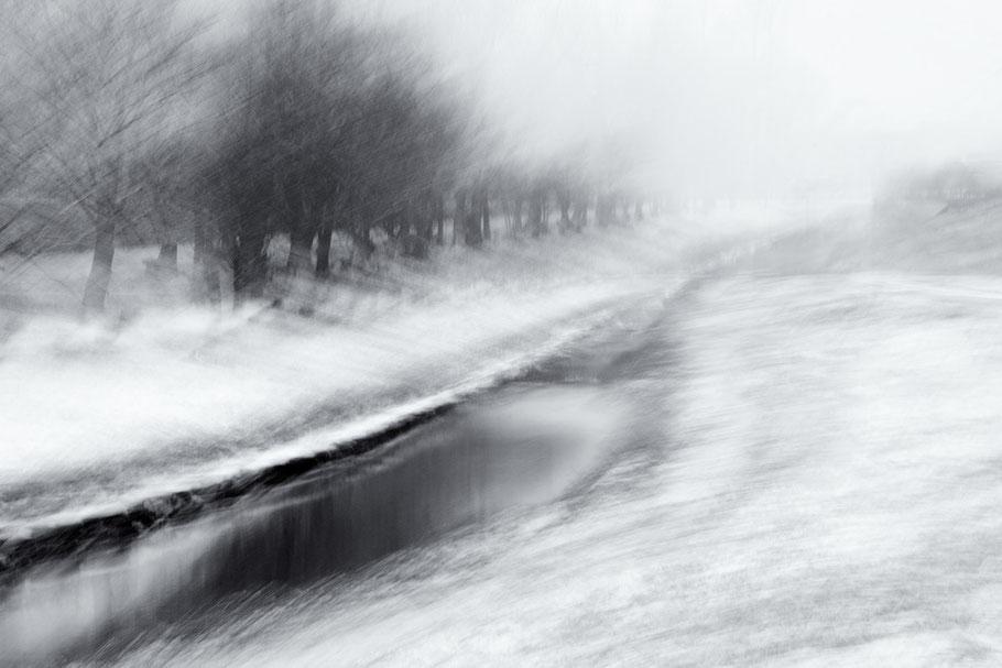 Bayern, Oberpfalz. Flutkanal zwischen Steinfels und Hütten. Aufnahme bei Schneegestöber. Schwarz-Weiss.