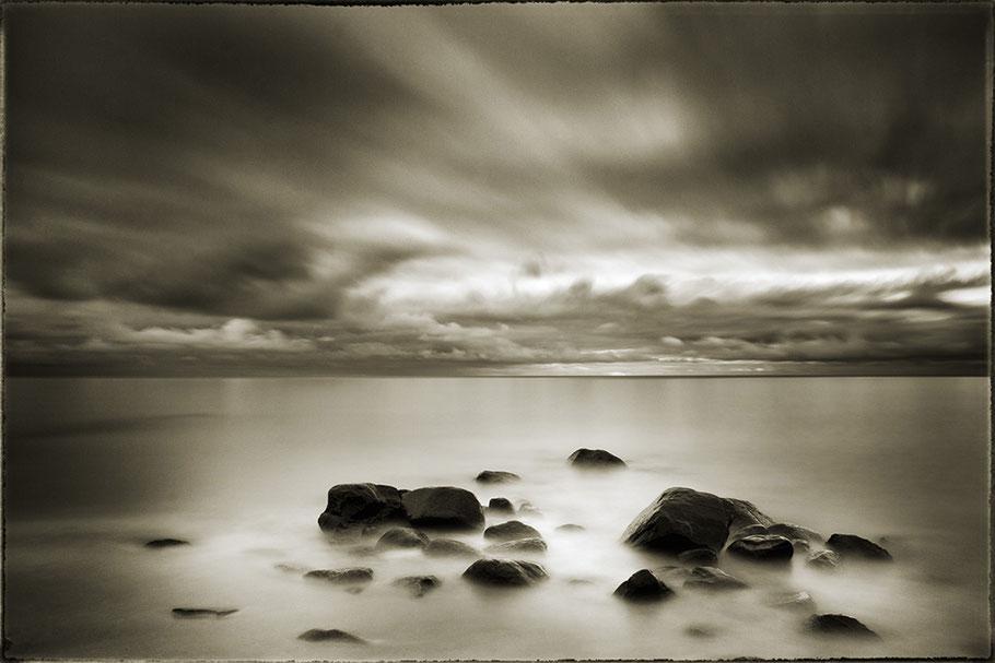 Insel Rügen Strand. Im Vordergrund Steine. Langzeitbelichtung, glatte Wasserfläche, ziehende Wolken. Leichte Sepia-Tonung