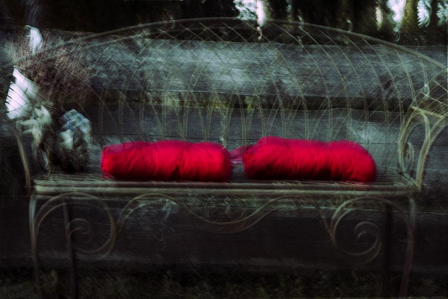 Gartenbank mit zwei roten Sitzkissen