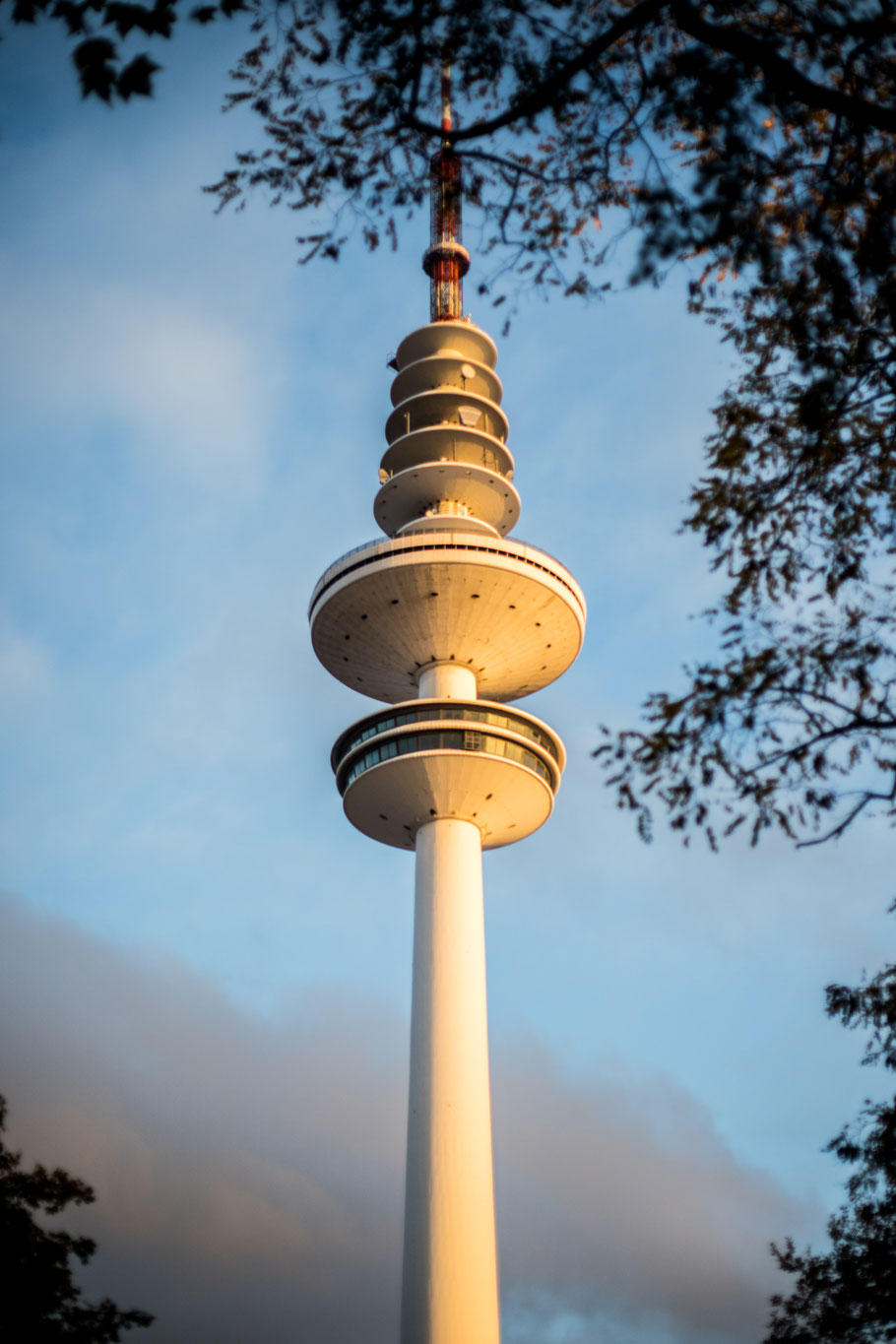 The Hamburg television tower against a partially cloudy autumn sky at sunset, surrounded by tree branches.