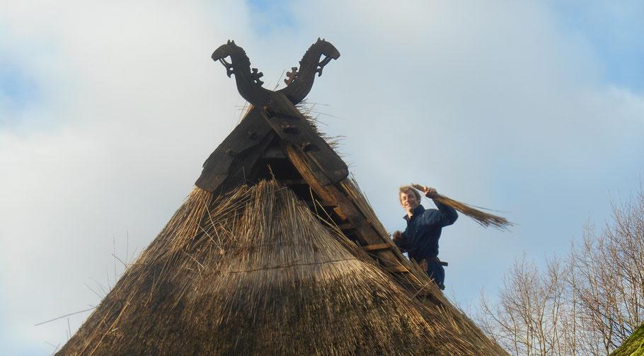 Jim aan het werk op zijn dak. De nok heeft authentieke geveltekens van het Wodansros Sleipnir met op diens rug de goddelijke raven Hugin en Munin.