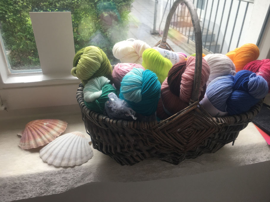 Körbchen mit Creative Bio Merino Sockenwolle, handgefärbt, in den Farben Grün Blau, Türkis, Einhorn Beige, Rot und Orange.