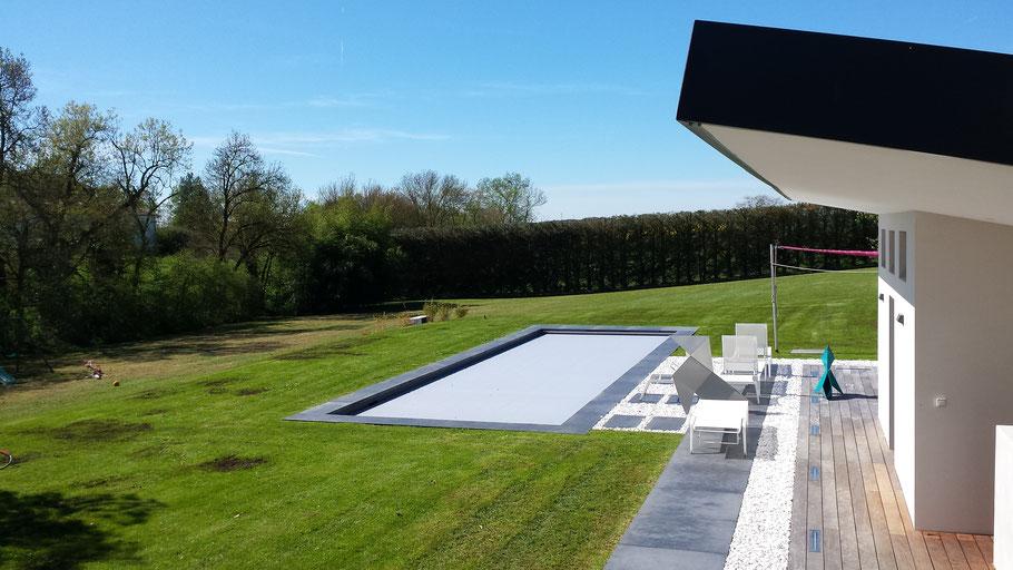 tour de piscine engazonné avec allée en gravier blanc et dalle grise . haie d'une grande hauteur et longueur taillée.