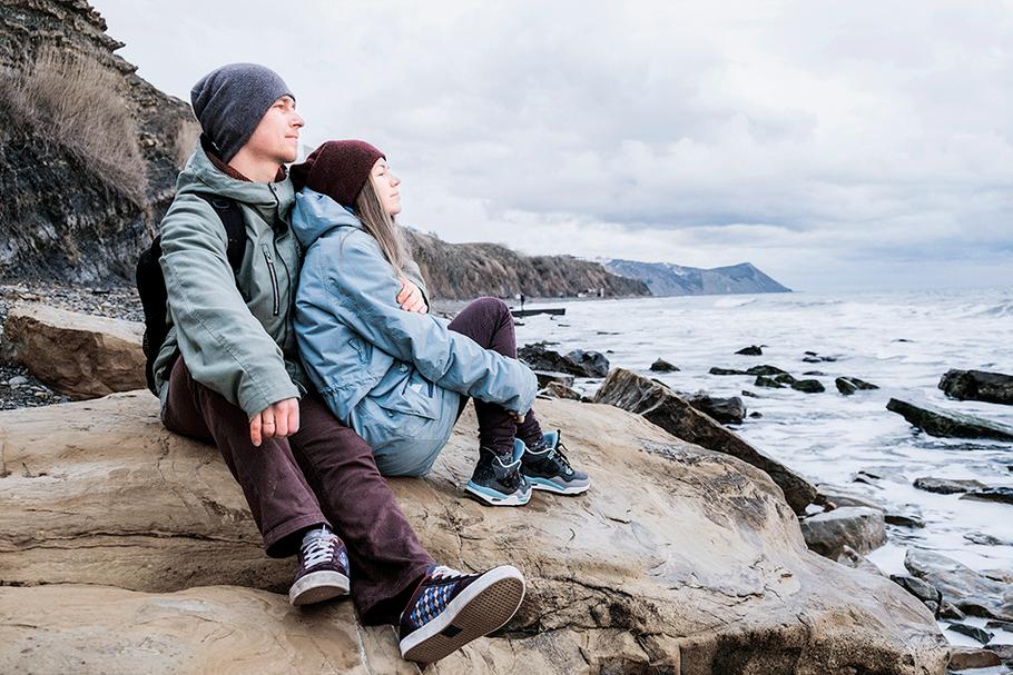 Pärchen sitzt chillig auf Felsen am Meer gesund dank metavirulent