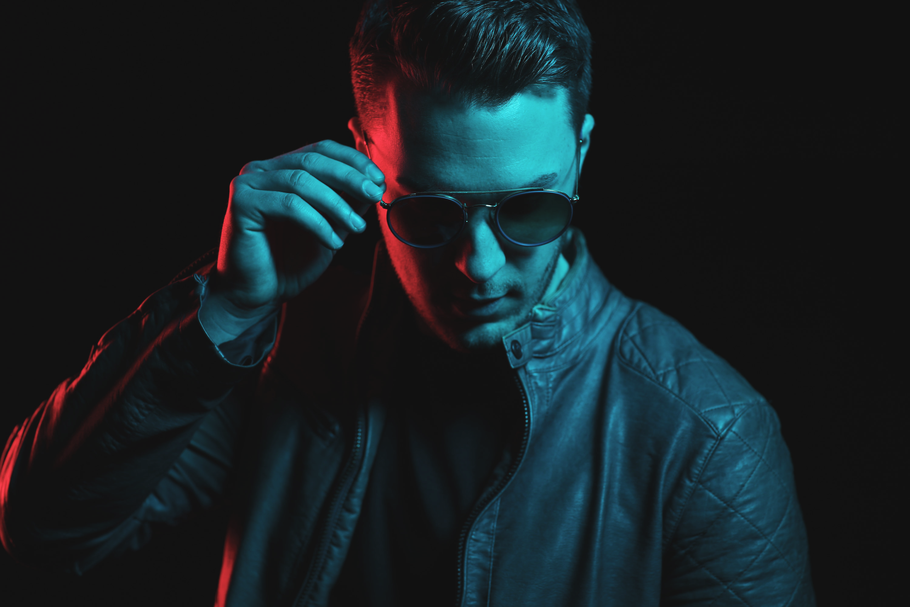 DJ Bamberg Nitronic Promotion Bild mit Sonnenbrille und Lederjacke. Aufnahme in Rot/Blauer Szene.