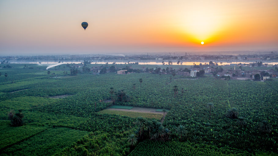 Sunrise from a balloon over Thebes and Nile river