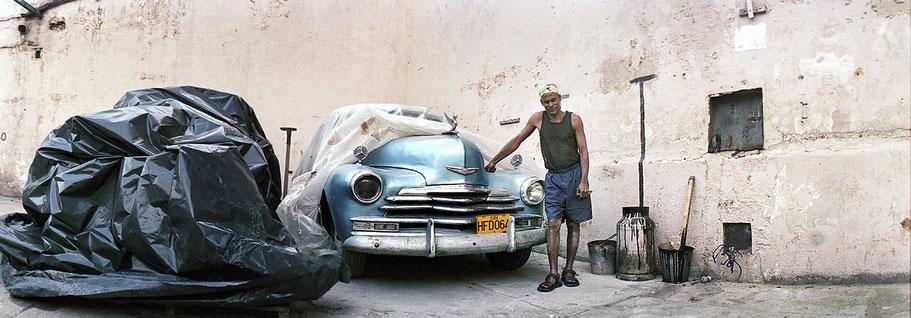 Mann zeigt blauen Oldtimer im Hinterhof in der Altstadt von Havanna als Farbphoto im Panoramaformat, Cuba