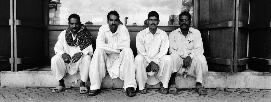 Vier Männer sitzend im Gold Souk in Dubai als Panorama-Photographie