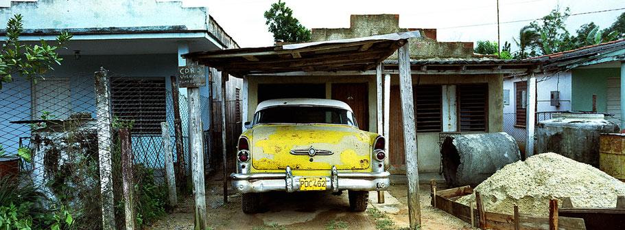 Gelber Oldtimer  steht vor einem Haus in der Zona 86  als Farbphoto im Panoramaformat, Cuba