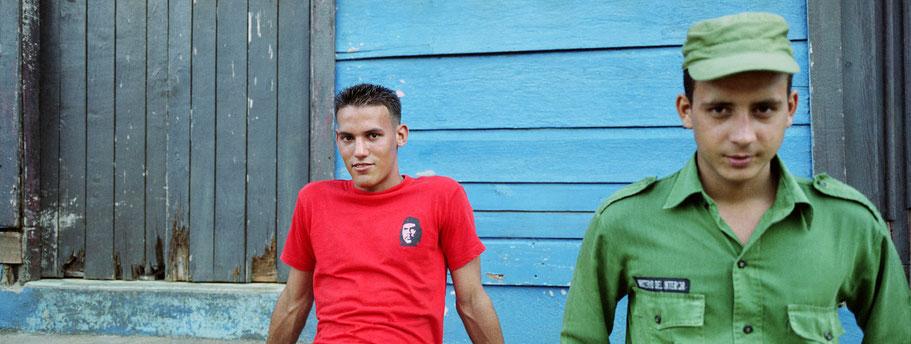 Zwei junge Cubaner sitzen vor einem blauen Haus in Baracoa als Panorama-Photographie